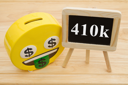 Learning how to save for your retirement, A coin bank on a desk with chalkboard with text 401k