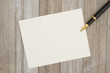blank spaces: A blank greeting card on weathered wood and a pen with copy space for your message