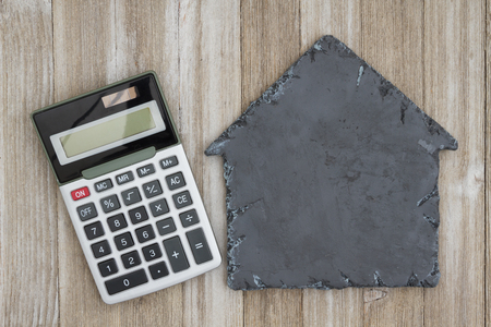 space wood: House shaped chalkboard with calculator on weathered wood with copy space for your message