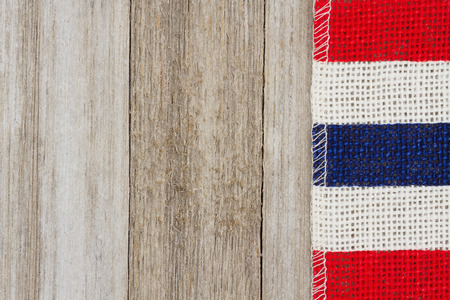 blank spaces: Red, white and blue pip burlap ribbon on weathered wood background with copy space for your message Stock Photo