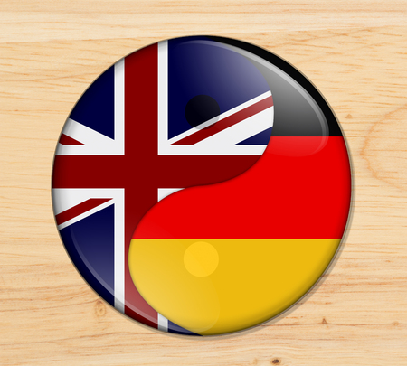 Britain and Germany working together, The British flag and German flag on a yin yang symbol on wood Reklamní fotografie