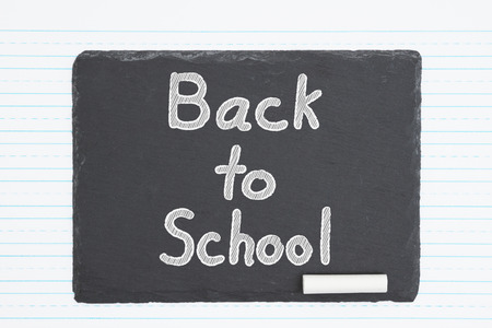 Back to School hand lettering text on weathered old chalkboard and retro lined paper