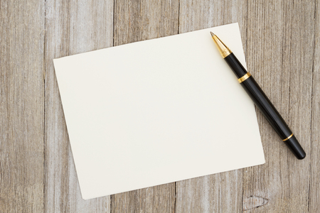 A blank greeting card on weathered wood and a pen with copy space for your message