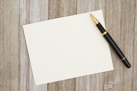 Een lege wenskaart op verweerde hout en een pen met kopie ruimte voor uw bericht