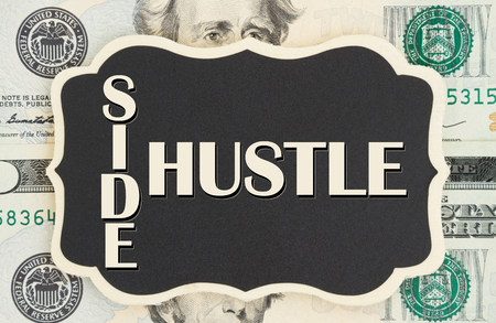 Geld verdienen met je zij drukte, Side Hustle-tekst op schoolbord op VS twintig dollarbiljetten