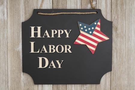 Gelukkige Dag van de Arbeid tekst op hangende schoolbord met een vlag ster op verweerde houten muur