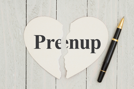 Writing up your prenuptial agreement, Heart-shape card on weathered wood background with text Prenup on each piece of the card Stok Fotoğraf