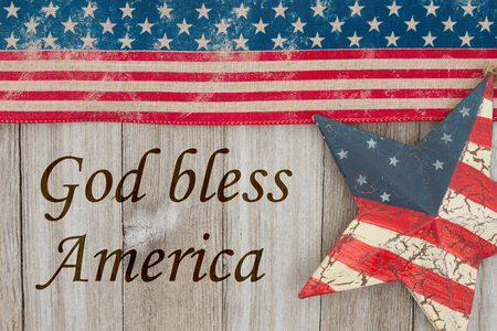 America patriotic message, USA patriotic old flag and a star and weathered wood background with text God Bless the USA