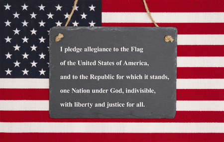 The pledge of allegiance written on a weathered chalkboard over the United States of America flag