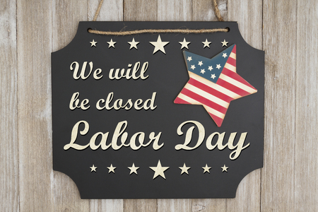 We will be closed Labor Day text on a chalkboard with patriotic USA red and blue star on weathered wood Stock fotó