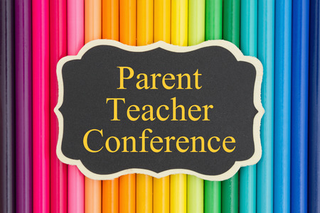 Parent Teacher Conference text on a chalkboard with colorful pencil crayons