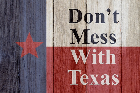 A rustic old Texas message, Texas flag on weathered wood background with text Don't mess with Texas Imagens