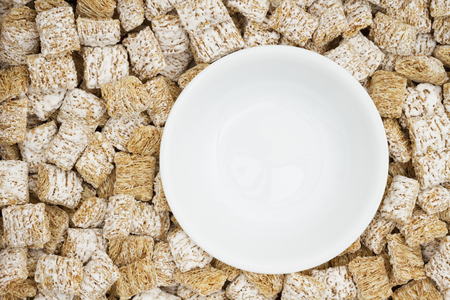 Whole grain wheat cereal with a white bowl