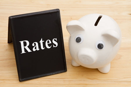 Knowing about the interest rates, A piggy bank with retro freestanding chalkboard on a wood desk with text Rates Stock Photo