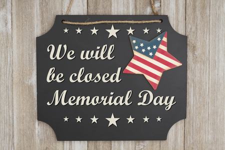 We will be closed Memorial Day text on a chalkboard with patriotic USA red and blue star on weathered wood Foto de archivo