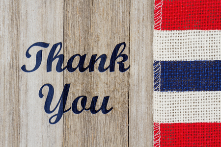 Thank you text with red, white and blue pip burlap ribbon on weathered wood