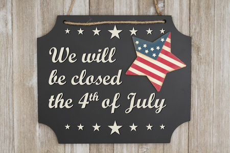 We will be closed he 4th of July text Independence Day on a chalkboard with patriotic USA red and blue star on weathered wood Фото со стока