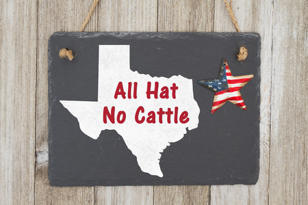 A rustic old Texan saying, A retro chalkboard with a vintage USA star hanging on weathered wood background with text All Hat No Cattle Foto de archivo