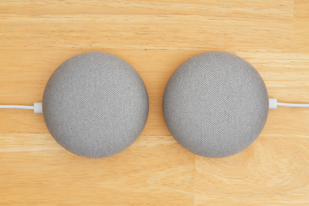 South Carolina, USA Oct 2018. Illustrative editorial image of two Google home devices on a wood desk Imagens