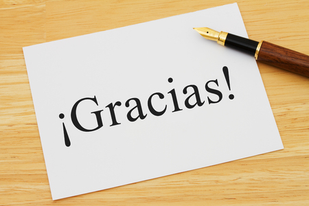 A white card on a desk with a pen with text Gracias