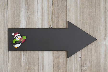 Arrow chalkboard sign with a Christmas penguin on weathered wood with copy space for your message