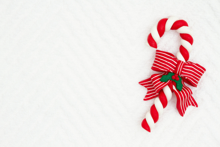 Christmas candy cane with a bow on white chevron textured fabric background that you can use as a mock up for your message for Christmas