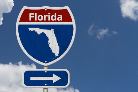 Road trip to Florida, Red, white and blue interstate highway road sign with word Florida and map of Florida with sky background