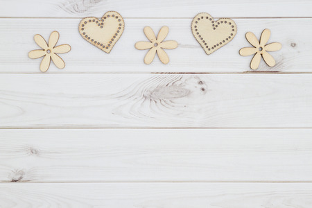 Old fashion love background with wooden hearts and flowers on weathered wood with copy space for your message