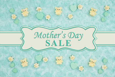 Mothers Day Sale message with teal candy hearts, teddy bears and rose buds on a teal plush fabric with ribbon 스톡 콘텐츠