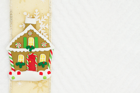 Christmas gingerbread house with gold snowflake ribbon on white chevron textured fabric background that you can use as a mock up for your message for Christmas 免版税图像