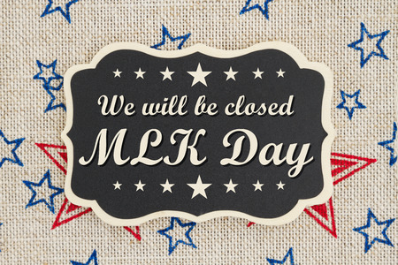 We will be closed MLK Day text on a chalkboard with patriotic USA red and blue stars on burlap