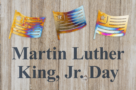 Martin Luther King Day message text with USA patriotic metal flags on a weathered wood