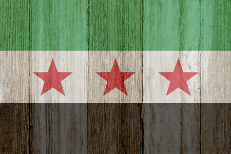 A rustic old Syrian flag on weathered wood Stockfoto