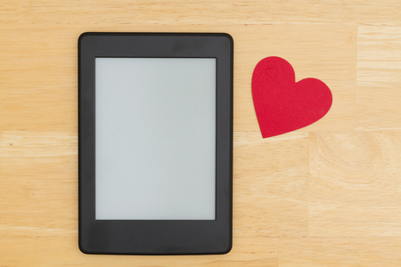 A blank e-reader on a desk with a heart that you can use as a mock up for your message