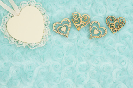 Wood heart with lace and wood hearts on pale teal rose plush fabric