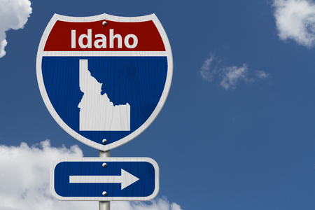 Road trip to Idaho, Red, white and blue interstate highway road sign with word Idaho and map of Idaho with sky