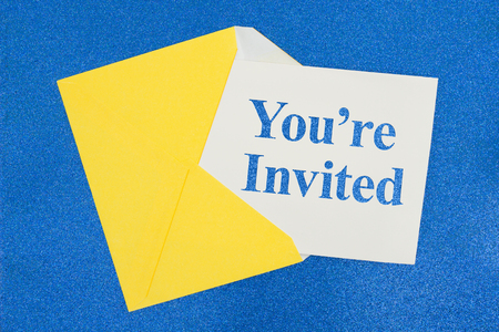 You're Invited message on white card with a yellow envelope on blue sparkle paper Stock Photo - 117969567