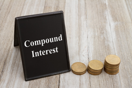 Understanding compound interest, Retro freestanding chalkboard  with gold coins on weathered wood with text Compound Interest
