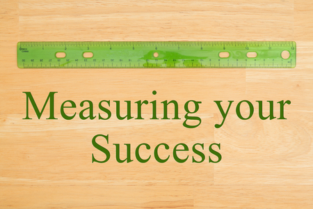 Measuring your Success message with a green plastic ruler on a wood desk