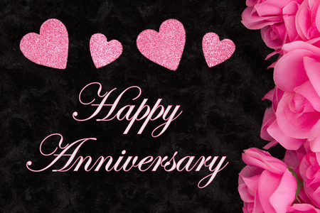 Happy Anniversary greeting with pink roses with hearts on black textured plush fabric