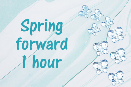 Spring forward 1 hour DST message with blue glass butterflies on  blue textured watercolor paper Stock Photo