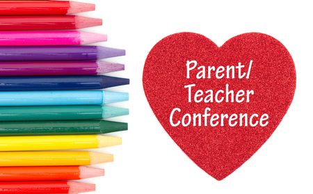 Parent Teacher Conference message on red heart with colored watercolor pencils isolated over white