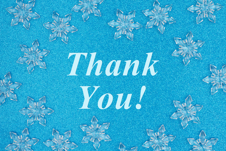 Thank you message with snowflakes on a blue glitter paper