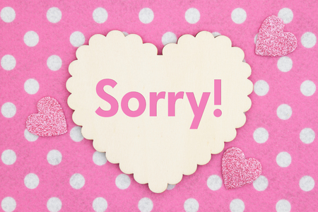 Sorry message on wood heart on pink and white polka dot fabric Foto de archivo