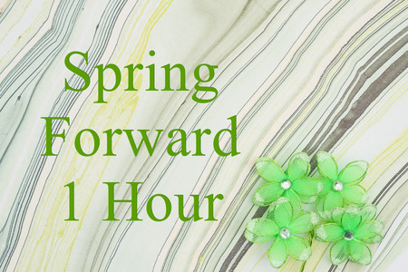 Spring forward 1 hour DST message green flowers on textured watercolor paper Stock Photo