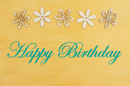 Happy Birthday greeting with wood flowers on hand painted distressed gold canvas Stockfoto