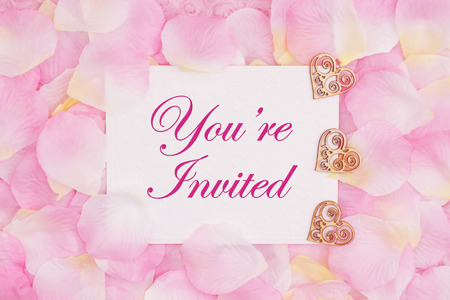 Youre invited greeting card with wood hearts and rose flower petals