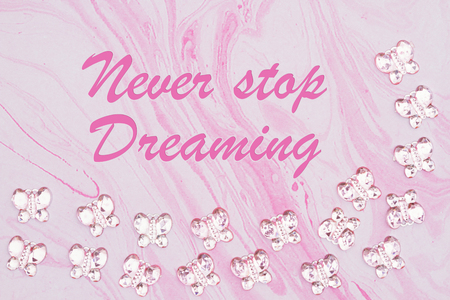 Never Stop Dreaming message with pink glass butterflies on  pink textured watercolor paper Stock Photo