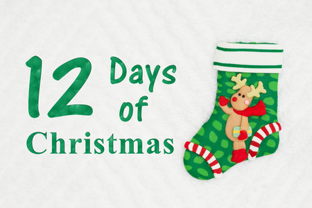 The 12 days of Christmas with a Christmas stocking with a reindeer on white chevron textured fabric