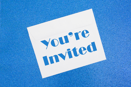 Youre Invited message on white envelope on blue sparkle paper